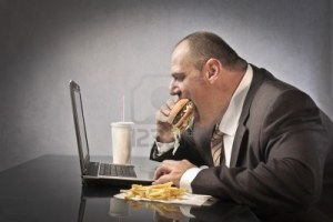 11571339-empresario-de-grasa-comer-comida-basura-delante-de-un-ordenador-portatil
